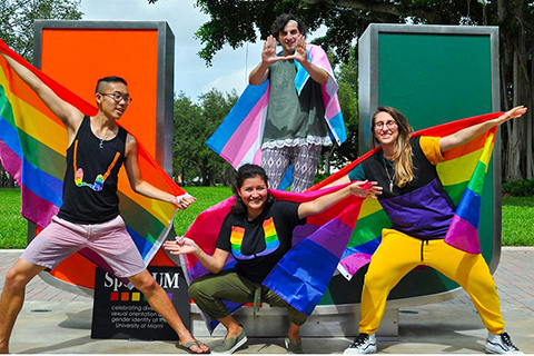 LGBTQIA+ student organization members pose in front of the U statue